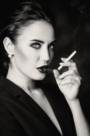 A portrait of a beautiful sexy woman wearing a black blazer smoking cigarette. Fashion, style, beauty. Zdjęcie Seryjne