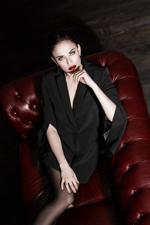 A portrait of a beautiful sexy woman wearing a black blazer posing on the leather sofa. Fashion, style, beauty.