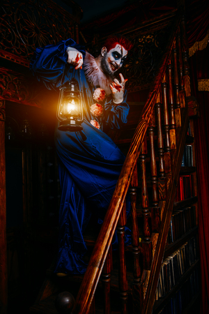 A portrait of an angry crazy clown from a horror film with a lantern on the stairs. Halloween, carnival. Stock Photo - 129686485