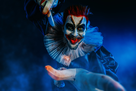 A portrait of an angry crazy clown from a horror film with a knife. Halloween, carnival. 写真素材