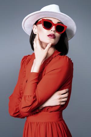 모자와 선글라스를 쓴 아름다운 여성의 초상화. 패션, 스타일, 뷰티, 광학.