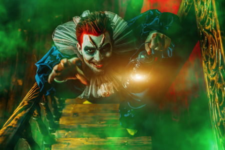 A portrait of an angry crazy clown from a horror film with a lantern on the stairs. Halloween, carnival.
