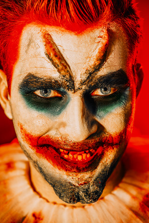 A close up portrait of a smiling clown from a horror film. Halloween, carnival.