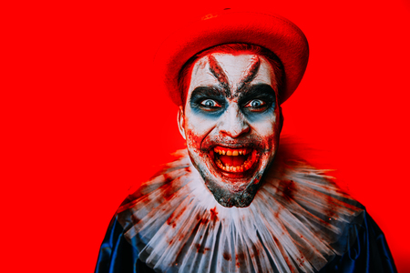 A portrait of an angry crazy clown from a horror film over the yellow background. Halloween, carnival.