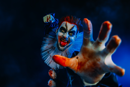 A portrait of an angry crazy clown from a horror film with a knife. Halloween, carnival. Reklamní fotografie