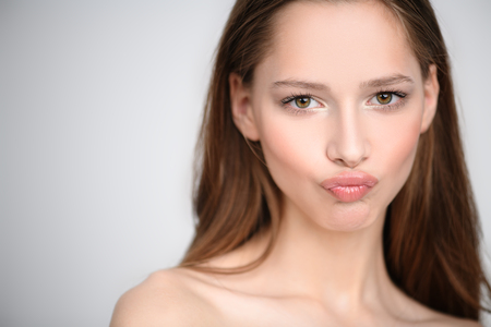 A close up portrait of a pretty young girl posing in the studio over the white background and making funny grimace. Beauty, cosmetics, skincare.