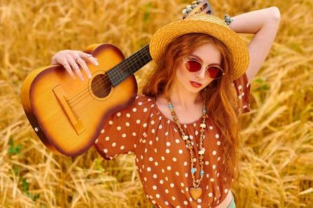 Glückliches Hippie-Mädchen steht mit ihrer Gitarre auf einem Weizenfeld. Geist der Freiheit und Unabhängigkeit.