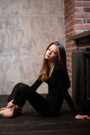 A portrait of a smiling young woman posing on the floor. Beauty, fashion.