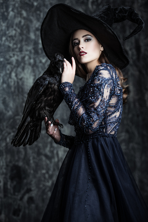 A witch in hat and dress with a raven. Halloween. Celebration.