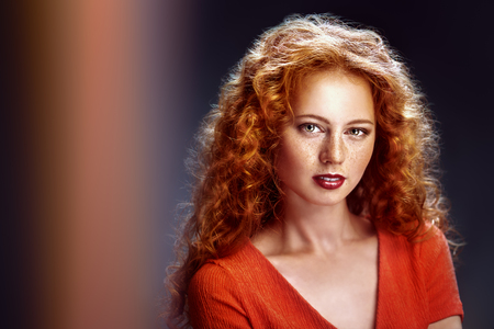 Beauty portrait. Charming girl with long red curly hair over black background. Hair care, hair coloring. Copy space.