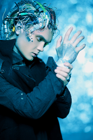 Cyborg looks at his hand. Biological human robot with wires implanted in the head. Technologies of the future. Zdjęcie Seryjne
