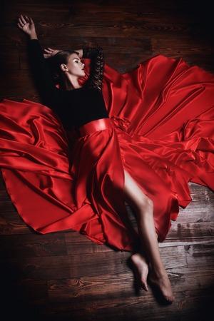 Un portrait en pied d'une belle dame dans une longue jupe rouge allongée sur un plancher en bois. Beauté, mode. Danse latino.