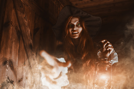 A portrait of a redhead witch with a lantern near the wooden house. Magic, dark force, spell. Stock Photo