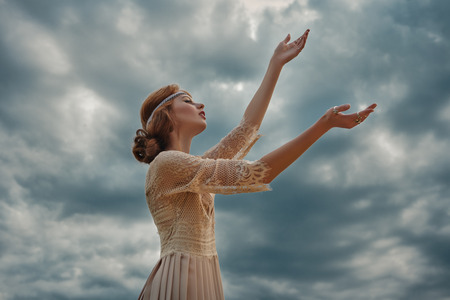 Romantic young woman with beautiful red hair dreamily raises her hands to the sky. Stock fotó