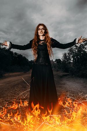 Un retrato de una bruja enojada cerca del fuego. Magia, fuerza oscura, hechizo.