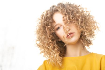 Portret uroczej młodej dziewczyny o kręconych jasnych włosach w żółtej sukience. Moda, uroda.