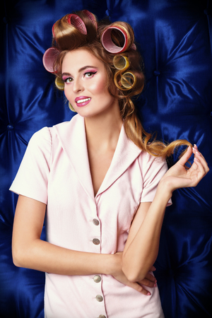 Charming young woman with curlers in her hair posing over blue luxurious satin background. Beauty, fashion concept. Pin-up style.