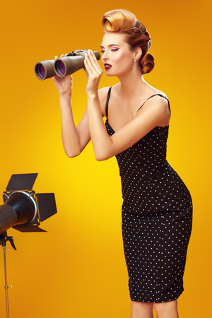 Beautiful glamorous woman in elegant evening dress looking through binoculars. Pin-up style in clothes, hair and make-up. Yellow background. 写真素材
