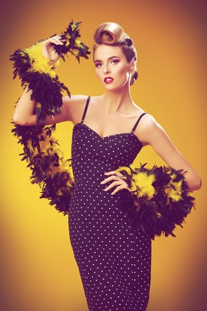 Beautiful glamorous woman in elegant evening dress. Pin-up style in clothes, hair and make-up. Yellow background. 写真素材
