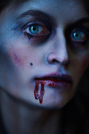 Halloween. Close-up portrait of a bloodthirsty woman vampire in the old abandoned castle. Vintage style. Stock fotó
