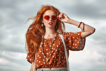 Portrait of a beautiful red-haired girl over sky background. Hair coloring. Hippie style. Bohemian style.