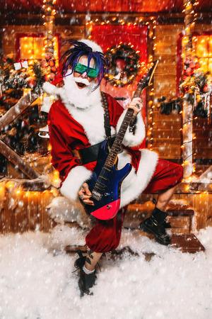 Cooler Rocker im Weihnachtsmannkostüm und leuchtende Brille spielt Gitarre in der Nähe eines festlich geschmückten Hauses.