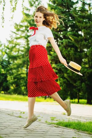 A portrait of a cute romantic girl walking in the park. Summer casual fashion, beauty.