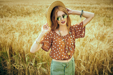 Portrait of a modern hippie girl in a wheat field. Bohemian style. Stockfoto