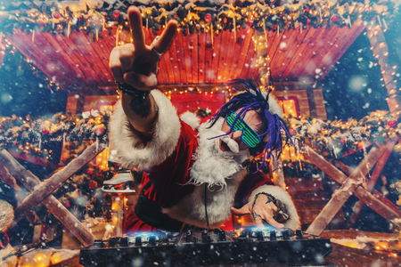 Ð¡razy punk Santa Claus in luminous glasses and headphones holds a party near his house decorated with lights. Christmas cool party.