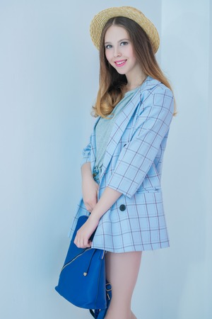 A portrait of a stylish bright fashionable happy girl posing in the studio over the light blue background. Summer casual fashion.