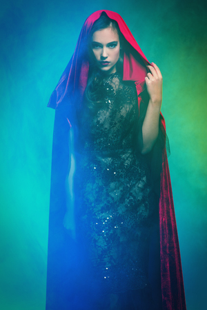 A beautiful lady in a red cloak. Halloween. Celebration.