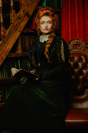 Historical reconstruction of the Victorian era. Portrait of an elegant woman in vintage  dress and hairdo reading a book in her library. Baroque era. Banque d'images - 130208278