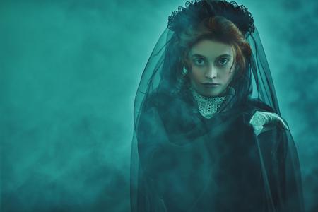 Porträt einer viktorianischen Frau in Trauer. Schwarze Witwe in einer Atmosphäre von Geheimnis und Mystik. Halloween.