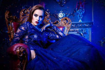 A charming vampire lady is sitting at a armchair in classic interior. Beauty. Fashion. Stock Photo
