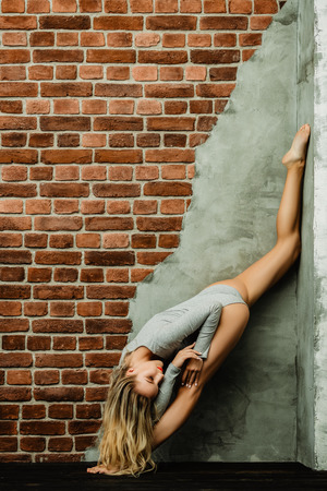 A full length portrait of a flexible young woman stretching near the wall. Dancer, flexibility. Stockfoto