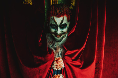 Un retrato de un payaso loco enojado de una película de terror sobre la cortina roja. Halloween, carnaval. Foto de archivo