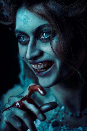 Halloween. Close-up portrait of a bloodthirsty woman vampire in the old abandoned castle. Vintage style. 写真素材