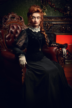 The Victorian era concept. Beautiful woman in elegant historical dress and hairstyle sitting in an armchair by a fireplace in her palace. Baroque. Fashion. Banque d'images - 130321298