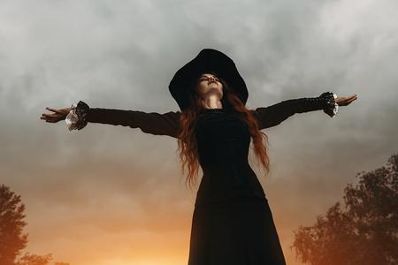 Un retrato de una bruja enojada cerca del bosque. Magia, fuerza oscura, hechizo.