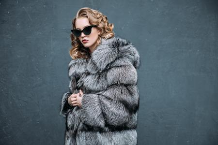 Ein Porträt einer schönen Frau, die einen Pelzmantel mit Kapuze und Sonnenbrille trägt. Schönheit, Wintermode, Stil. Standard-Bild