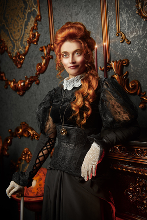 The Victorian era concept. Beautiful woman in elegant historical dress and hairstyle posing in vintage interior. Baroque. Fashion. Stockfoto
