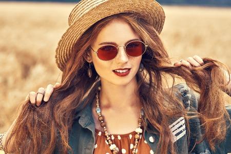 Retrato de una chica hippie moderna en un campo de trigo. Estilo bohemio. Foto de archivo