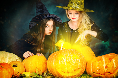 Two little witches playing with pumpkins. Halloween party. Archivio Fotografico