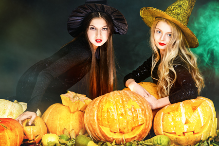 Two little witches playing with pumpkins. Halloween party.