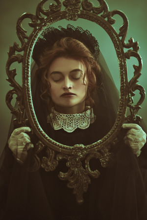 Portrait of a sad woman with closed eyes in a black veil in an old vintage frame . Black widow in an atmosphere of mystery and mysticism. Halloween.