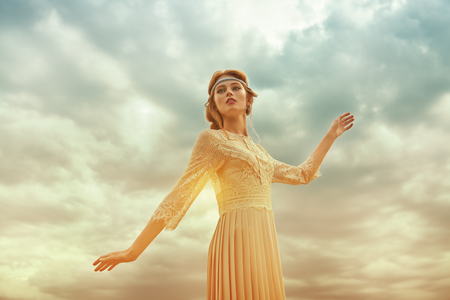 Romantic young woman with beautiful red hair dreamily raises her hand to the sky.