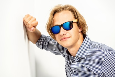 A portrait of a young brutal  man in a checked shirt and sunglasses posing indoor. Men fashion, beauty, optics. Reklamní fotografie