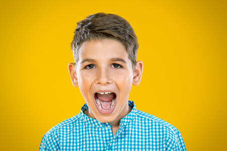 A portrait of a cheerful young boy over the yellow background. Beauty, summer, fashion, emotions.