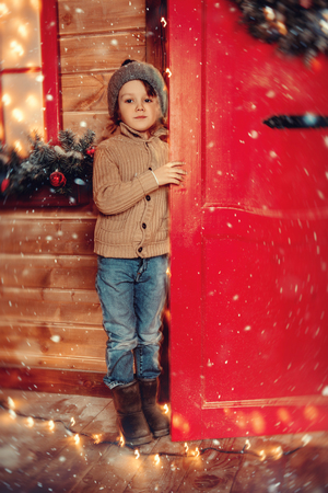 A little boy looking out of the house decorated for Christmas. Miracle time. Merry Christmas and Happy New Year.