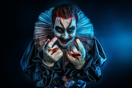 Un portrait d'un clown fou en colère d'un film d'horreur avec un marteau. Halloween, carnaval.